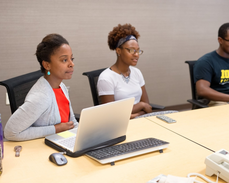 Black students sitting at a conference table, laptops open